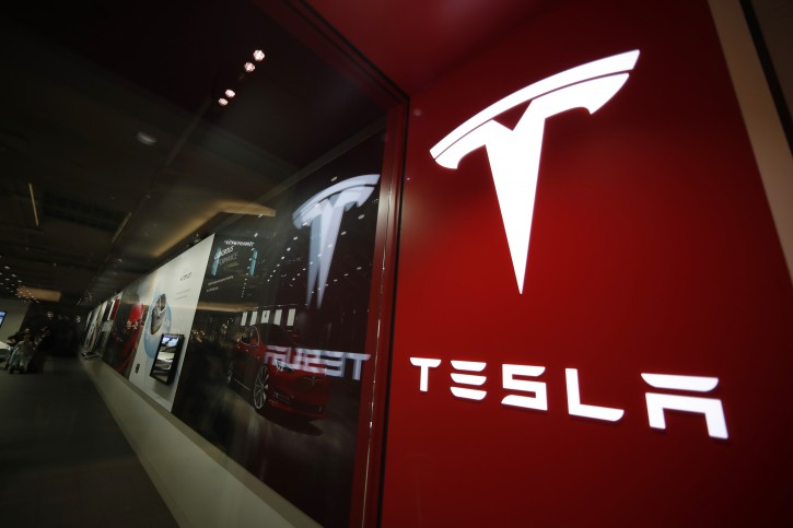 FILE--In this Saturday, Feb. 9, 2019, file photograph, a sign bearing the company logo stands outside a Tesla store in Cherry Creek Mall in Denver. (AP Photo/David Zalubowski, File)