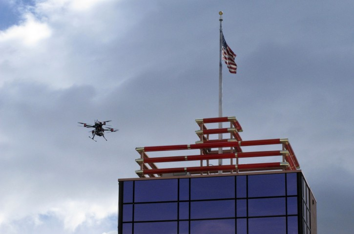 A drone flys over downtown Reno before landing on the Cal-Neva casino parking garage on Tuesday, May 21, 2019 as part of a NASA simulation to test emerging technology that someday will be used to manage travel of hundreds of thousands of commercial, unmanned aerial vehicles (UAVs) delivering packages. It marked the first time such tests have been conducted in an urban setting. (AP Photo/Scott Sonner)