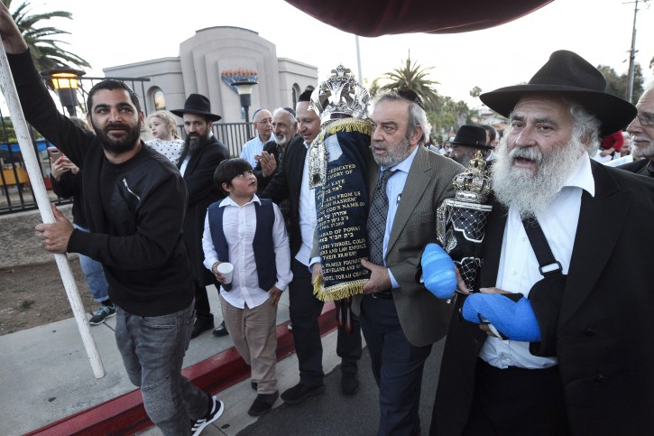 Howard Kaye, center, husband of  Lori Gilbert-Kaye, carries the new torah as Rabbi Yisarel Goldstein, right, and other members of the Chabad of Poway synagogue celebrate the completion of new torah dedicated to Lori Gilbert-Kaye, who was killed when a gunman attacked last April, at Chabad of Poway on Wednesday, May 22, 2019 in Poway, California. AP