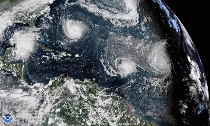 This Sept. 11, 2018 enhanced satellite image made available by NOAA shows Tropical Storm Florence, upper left, in the Atlantic Ocean, Tropical Storm Isaac, center, and at right Hurricane Helene. (NOAA via AP)