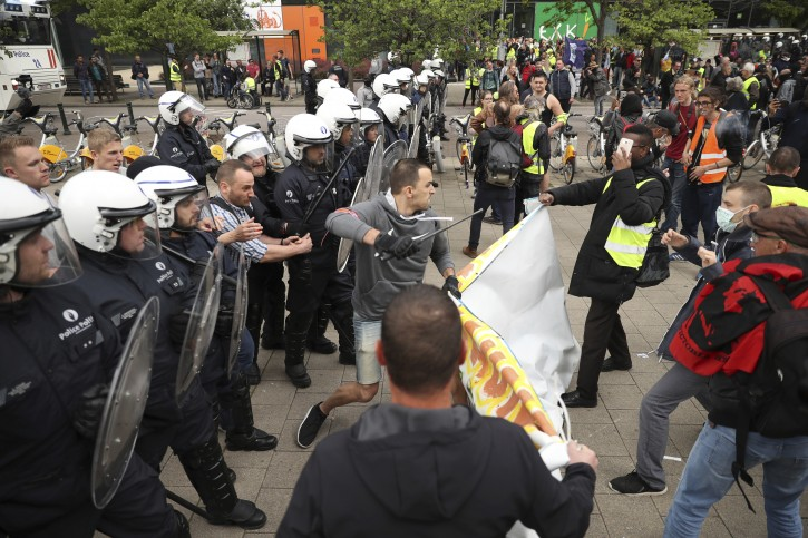 Police scuffle with yellow vest protestors and other groups during a demonstration in Brussels, Sunday, May 26, 2019. The demonstration took place as Belgium took to the polls to elect regional, national and European candidates. (AP Photo/Francisco Seco)