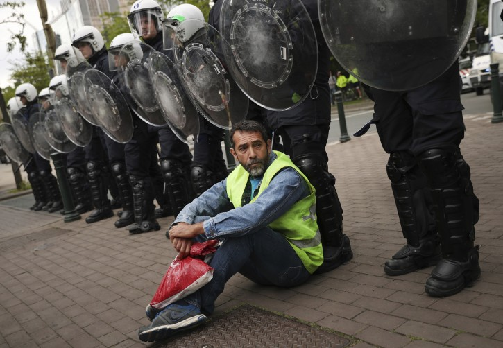 A yellow vest protestor sits in front of a line of police during a demonstration in Brussels, Sunday, May 26, 2019. The demonstration took place as Belgium took to the polls to elect regional, national and European candidates. (AP Photo/Francisco Seco)