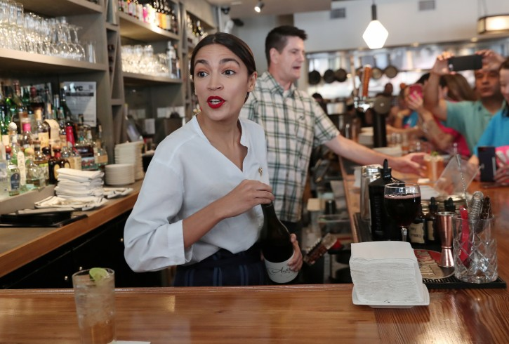 Rep. Alexandria Ocasio-Cortez (D-NY) serves drinks in support of One Fair Wage, a policy that would allow tipped workers to receive full minimum wage plus their tips in New York, at The Queensboro restaurant in the Queens borough of New York, U.S., May 31, 2019. REUTERS/Shannon Stapleton