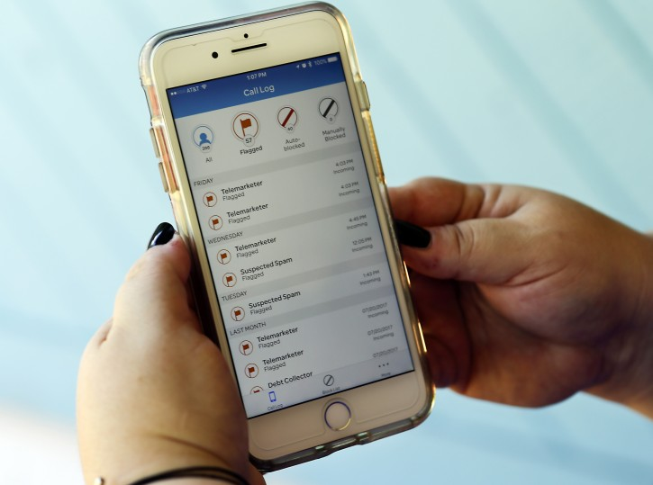 In this Tuesday, Aug. 1, 2017 photo, Jen Vargas checks out an AT&T app on her cell phone at her home in Orlando, Fla. The app helps locate and block fraudulent calls although some robocalls still get through. (AP Photo/John Raoux)