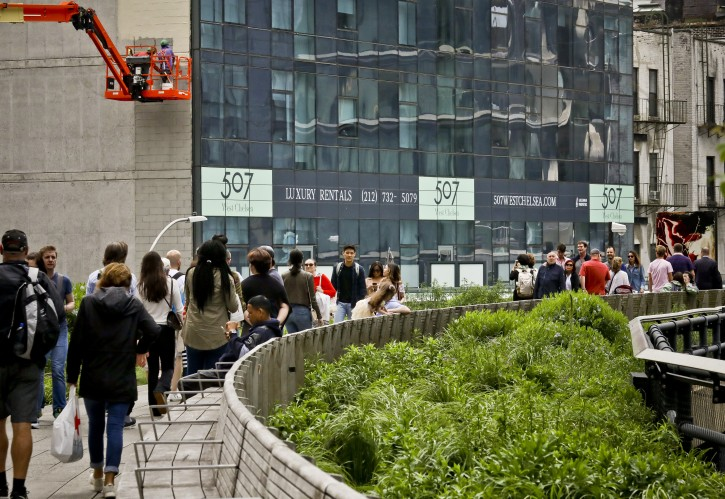 A new residential hi-rise display of signage for its luxury rentals, in view of visitors walking on the High Line, a walkway park created on abandoned rail tracks, Wednesday May 29, 2019, in New York.  (AP Photo/Bebeto Matthews)
