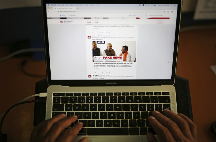 FILE - In this Tuesday, April 2, 2019, file photo, a man browses through the Twitter account of Alt News, a fact-checking website. A new survey says half of U.S. adults consider fake news a major problem, and they mostly blame politicians and activists for it. (AP Photo/Altaf Qadri, File)