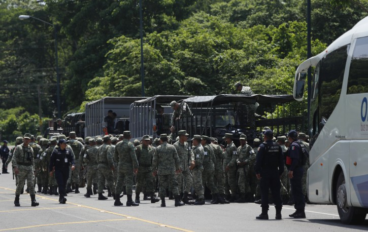 Police officers, marines, soldiers and immigration officials form up on the highway, in Metapa, Chiapas state Mexico, Wednesday, June 5, 2019. The law enforcement group arrived at the area to intercept a caravan of migrants that had earlier crossed the Mexico  Guatemala border. (AP Photo/Marco Ugarte)