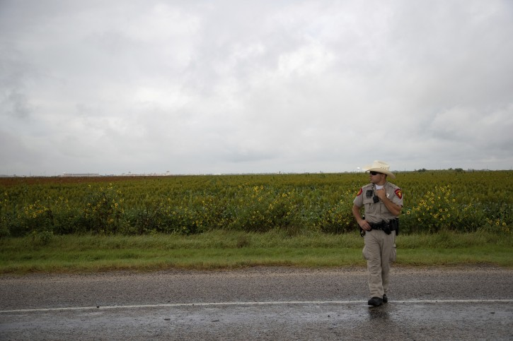 A police officer works on the scene of a fatal wreck that left six migrants dead and several others injured outside Robstown, Texas on Wednesday, June 5, 2019. (Courtney Sacco/Corpus Christi Caller-Times via AP)