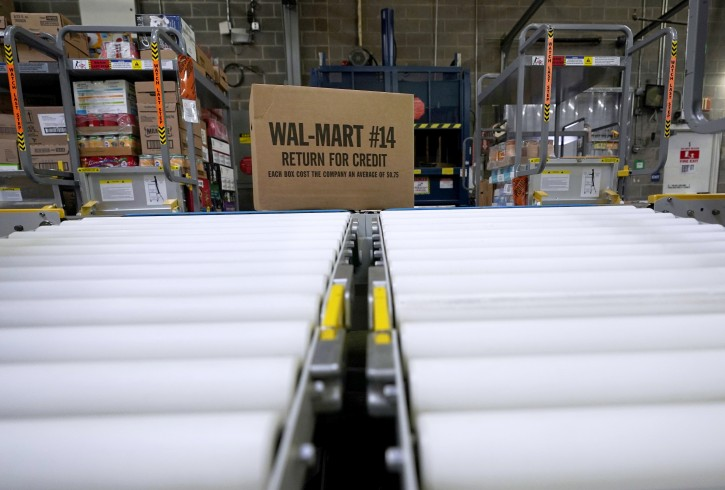 FILE- In this Nov. 9, 2018, file photo a box of merchandise is unloaded from a truck and sent along a conveyor belt at a Walmart Supercenter in Houston.  (AP Photo/David J. Phillip, File)