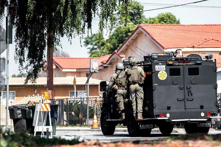 Los Angeles County sheriff's SWAT members get in to position to surround a home where an armed man is barricaded at a property in San Gabriel, Calif., Thursday, June 6, 2019.  (Watchara Phomicinda/The Press-Enterprise via AP)