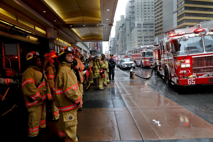 Firefighters respond to the scene near 52nd Street and 7th Ave., Monday, June 10, 2019, in New York, where a helicopter was reported to have crash landed on top of a building in midtown Manhattan. The New York City Fire Department says the pilot of the helicopter that crashed on the skyscraper rooftop has died. Gov. Andrew Cuomo told reporters that a fire began when the aircraft hit, but it is under control. He said there are no reports of injuries of people in the tower.(AP Photo/Mark Lennihan)