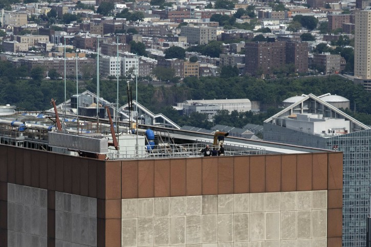 Law enforcement personnel work on the roof of the AXA Equitable building, Tuesday, June 11, 2019 in New York. A helicopter crashed Monday on the roof of the rain-shrouded Manhattan skyscraper, killing the pilot, Tim McCormack, of Clinton Corners, N.Y. (AP Photo/Mark Lennihan)