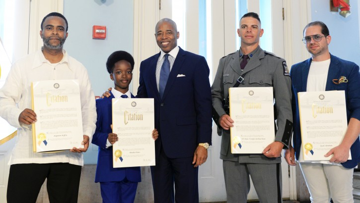 Borough President Adams delivers remarks at the Heroes of the Month ceremony, which featured honorees from March, April, and May of this year.(L-R)Hopeton Kiffin a subway conductor, 10 year old Obocho Peters a young entrepreneur, State Trooper Joshua Kaye, Jacob Abraham