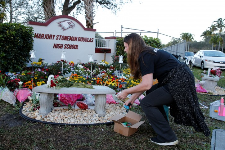 FILE PHOTO: A visitor places items on a memorial on the one year anniversary of the shooting which claimed 17 lives at Marjory Stoneman Douglas High School in Parkland, Florida, U.S., February 14, 2019.    REUTERS/Joe Skipper/File Photo