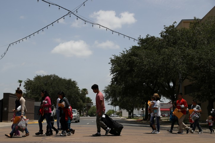 FILE - Undocumented immigrant families walk from a bus depot to a respite center after being released from detention in McAllen, Texas, U.S., July 4, 2018.  REUTERS/Loren Elliott/File Photo