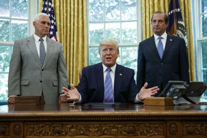 President Donald Trump, joined by Vice President Mike Pence, left, and Secretary of Health and Human Services Alex Azar, right, speaks during a signing ceremony in the Oval Office of the White House in Washington, Monday, July 1, 2019. (AP Photo/Carolyn Kaster)
