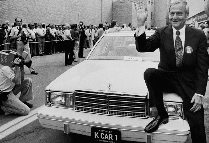 FILE - In this Wednesday, Aug. 7, 1980 file photo, Chrysler Corp. Chairman Lee Iacocca, sits on the hood of K Car Number One, a Plymouth Reliant, in Detroit. (AP Photo/Dale Atkins)