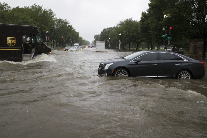 Heavy rainfall flooded the intersection of 15th Street and Constitution Ave., NW stalling cars in the street, Monday, July 8, 2019, in Washington. (AP Photo/Alex Brandon)