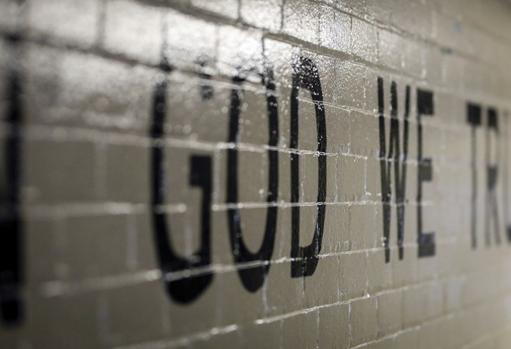 """This July 23, 2019 photo shows """"In God We Trust"""" stenciled in a wall at South Park Elementary in Rapid City, S.D. When students return to public schools across South Dakota this fall there should be a new message displayed in a common area, a cafeteria, entryway or other prominent location.(Adam Fondren/Rapid City Journal via AP)"""