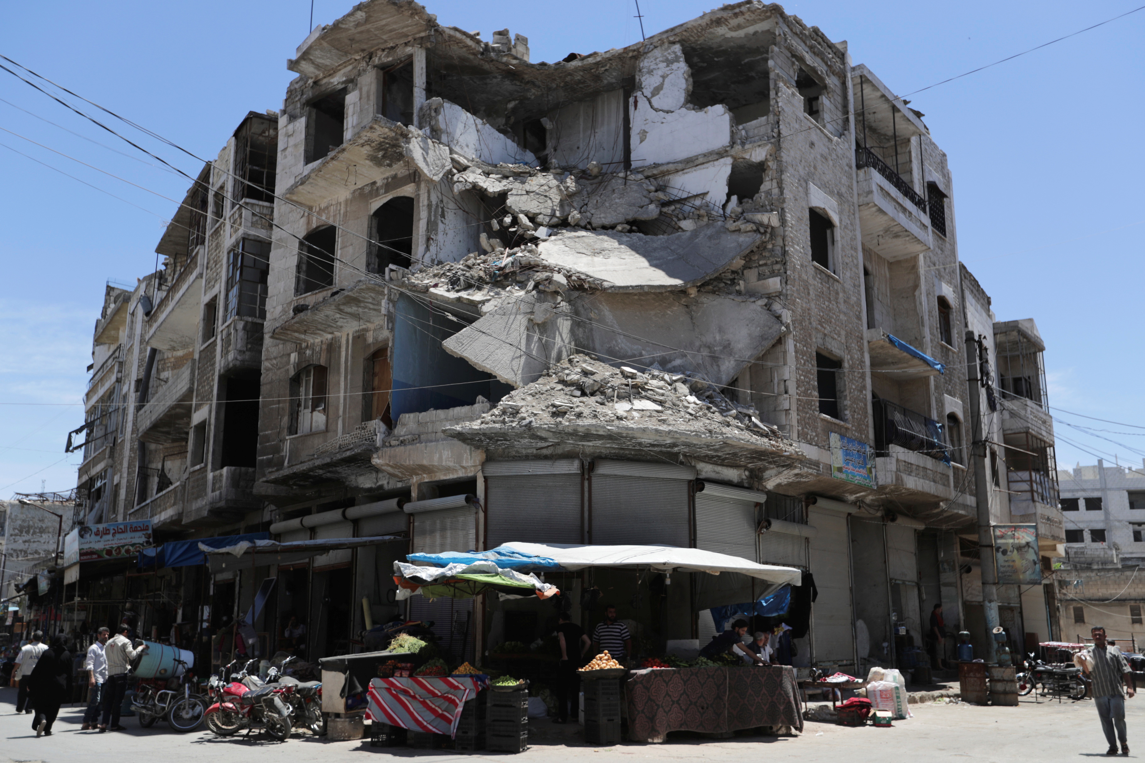 People walk past a damaged building in the city of Idlib, Syria May 25, 2019. REUTERS/Khalil Ashawi
