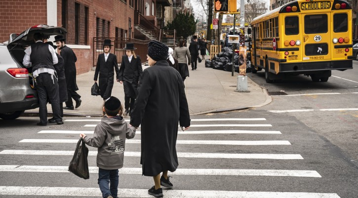Pedestrians walk past a yeshiva in the South Williamsburg neighborhood of Brooklyn, April 9, 2019. (Drew Angerer/Getty Images)