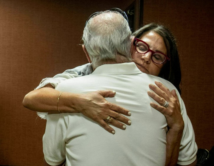 FILE - In this July 11, 2019 file photo, Tanya Gersh, a Montana real estate agent, embraces her father Lloyd Rosenstein following a hearing at the Russell Smith Federal Courthouse in Missoula.  AP