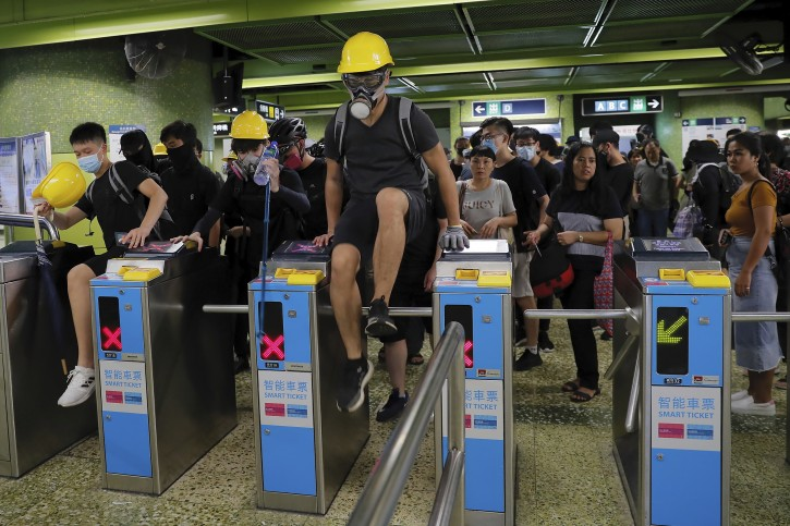 Protesters jump over MTR gates as they move to another destination during the anti-extradition bill protest in Hong Kong, Sunday, Aug. 11, 2019. Police fired tear gas late Sunday afternoon to try to disperse a demonstration in Hong Kong as protesters took over streets in two parts of the Asian financial capital, blocking traffic and setting up another night of likely showdowns with riot police. (AP Photo/Kin Cheung)