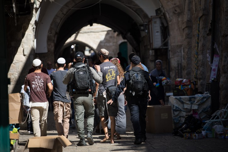 Police forces escort a group of Jewish boys in The Old City of Jerusalem as clashes brake out between Jews, Muslims and police on the Temple Mount and around its gates, as Jewish mark Tisha Beav mourning day and Muslims celebrate Eid al-Adha, on August 11, 2019. Photo by Hadas Parush/Flash90  **