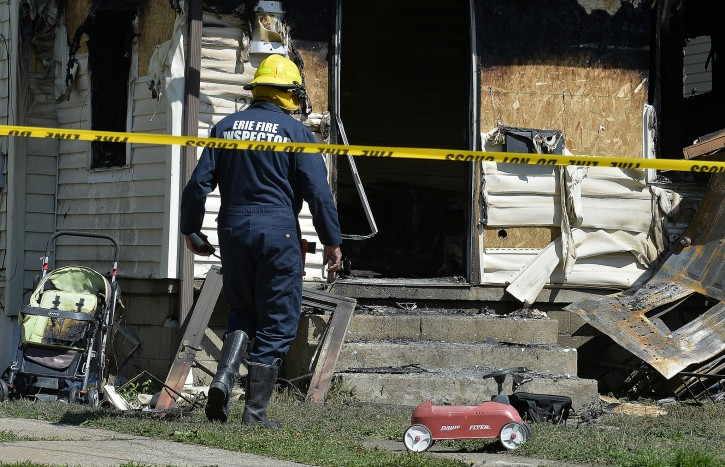 Erie Bureau of Fire Inspector Mark Polanski helps investigate a fatal fire at 1248 West 11th St. in Erie, Pa, on Aug. 11, 2019. Five children died in the early-morning fire.  (AP Photo/Erie Times-News, Greg Wohlford)