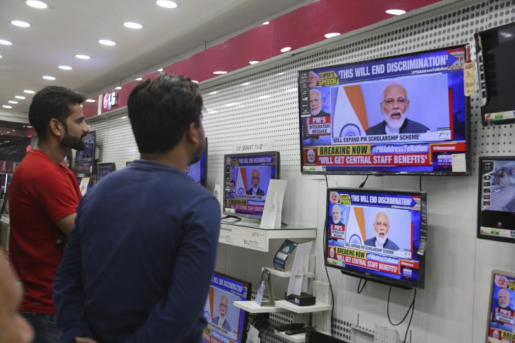 Indian people watch Prime Minister Narendra Modi message to the Nation, in Jammu, India, Thursday, Aug.8,2019.(AP Photo/Channi Anand)