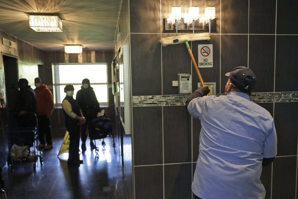Residents watch as members of the janitorial staff wipe down the lobby of a building in Co-op City in the Bronx borough of New York, Wednesday, May 13, 2020. Regular cleanings occur throughout the common areas of the buildings while the heavy disinfecting occurs in response to specific incidents, in this case reports of two coronavirus cases on the same floor. (AP Photo/Seth Wenig)