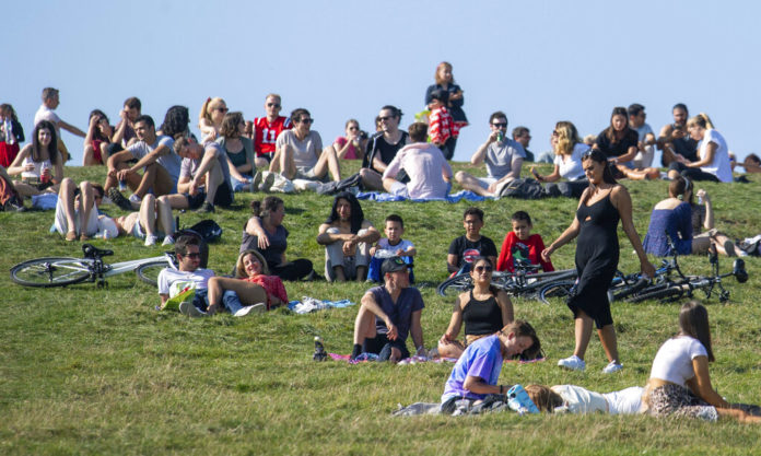 People enjoying the autumn sunshine on Primrose Hill, London, Sunday, Sept. 13, 2020. From Monday, social gatherings of more than six people will be banned in England — both indoors and outdoors — and Boris Johnson hinted that such restrictions will potentially remain in place until or through Christmas. (Dominic Lipinski/PA via AP)