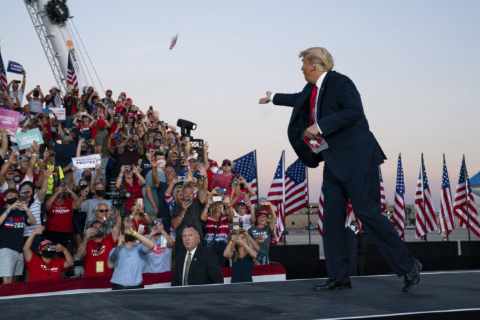 President Donald Trump throws face masks into the crowd as he arrives for a campaign rally at Orlando Sanford International Airport, Monday, Oct. 12, 2020, in Sanford, Fla. (AP Photo/Evan Vucci)